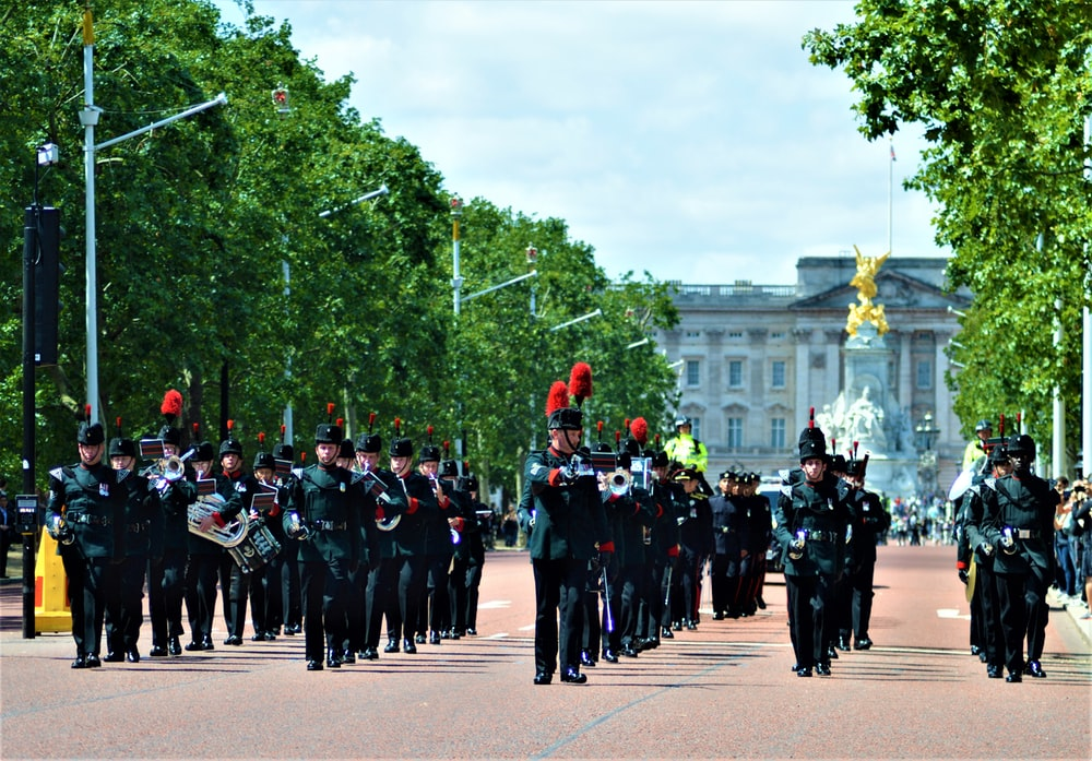 people parading on road beside Buckingham palace near trees