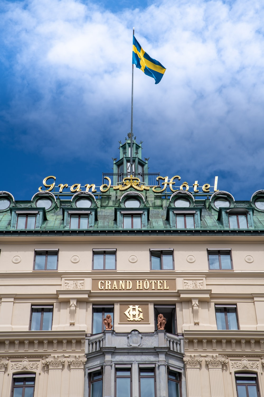 Sweden flag on top of pole on the roof of Grand Hotel building during day