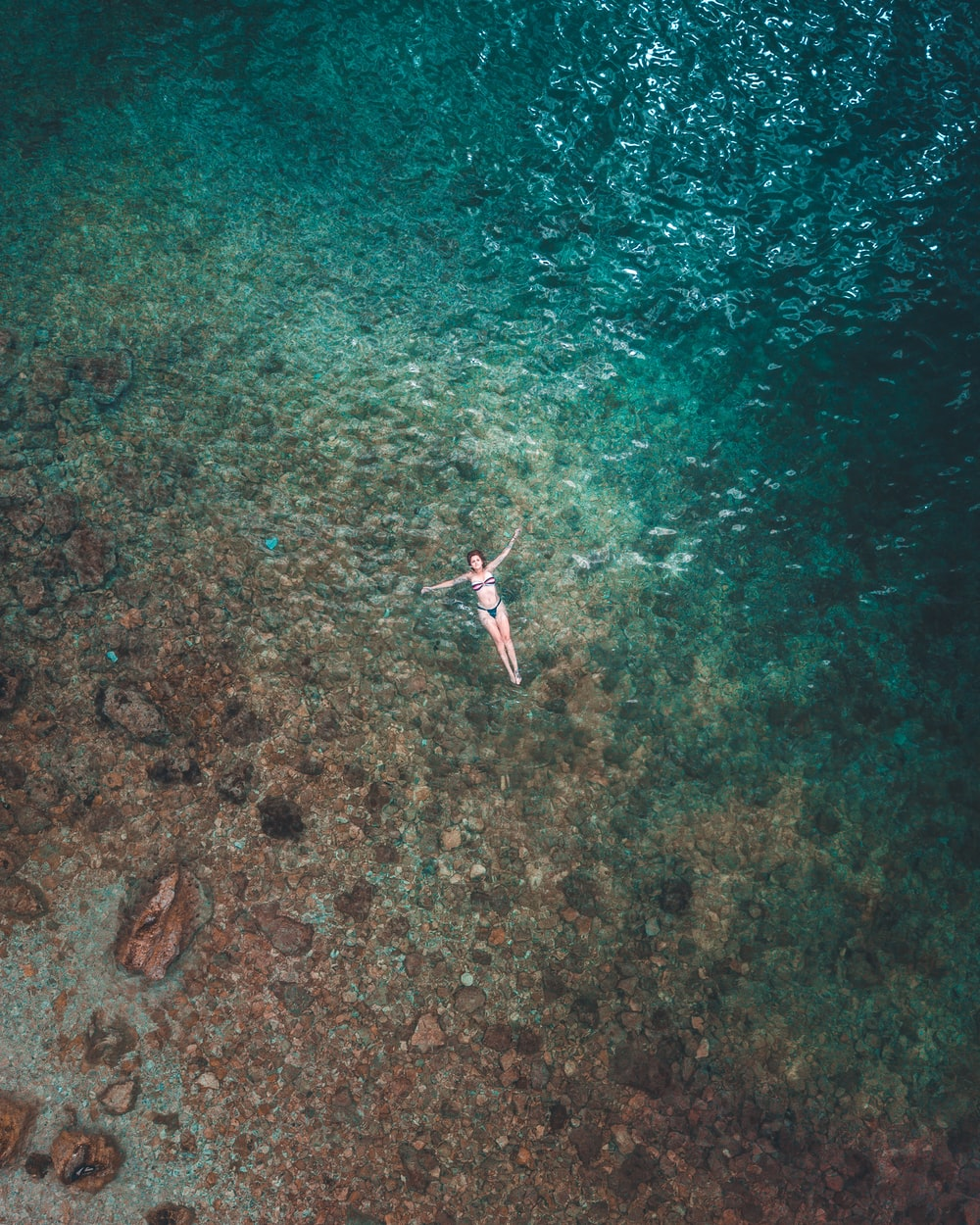 woman floating on water surface aerial photography