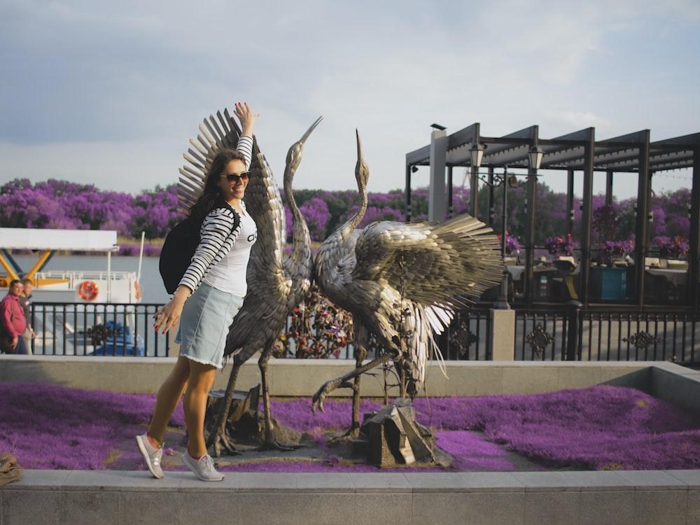 woman standing beside two bird statues