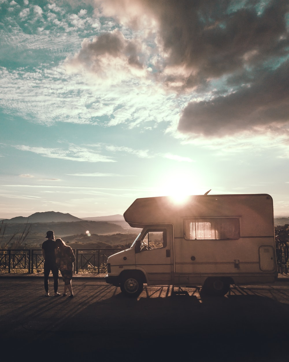 man and woman standing beside camper trailer on the street