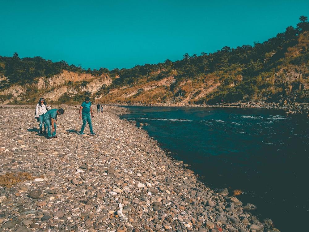 people in rocky lake shore