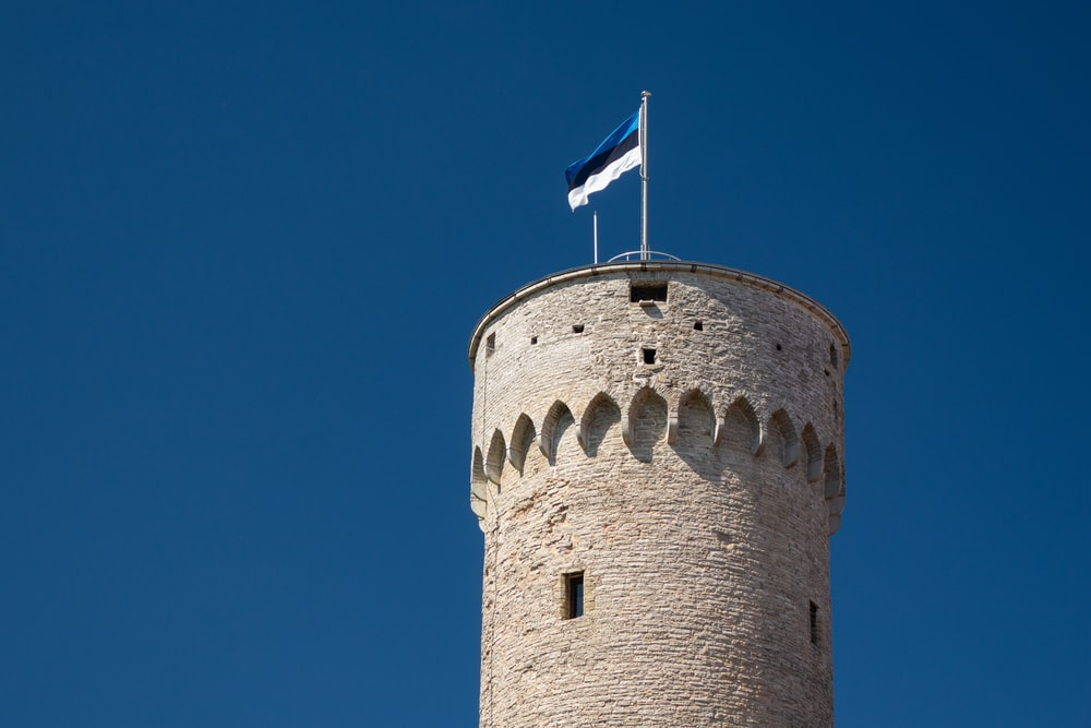brown concrete tower with blue, black, and white flag on top