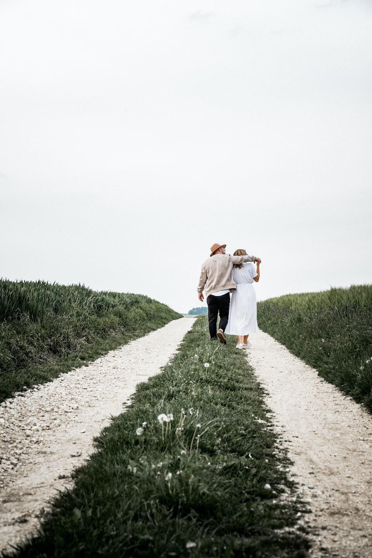 man and woman walking on pathway beside green bush