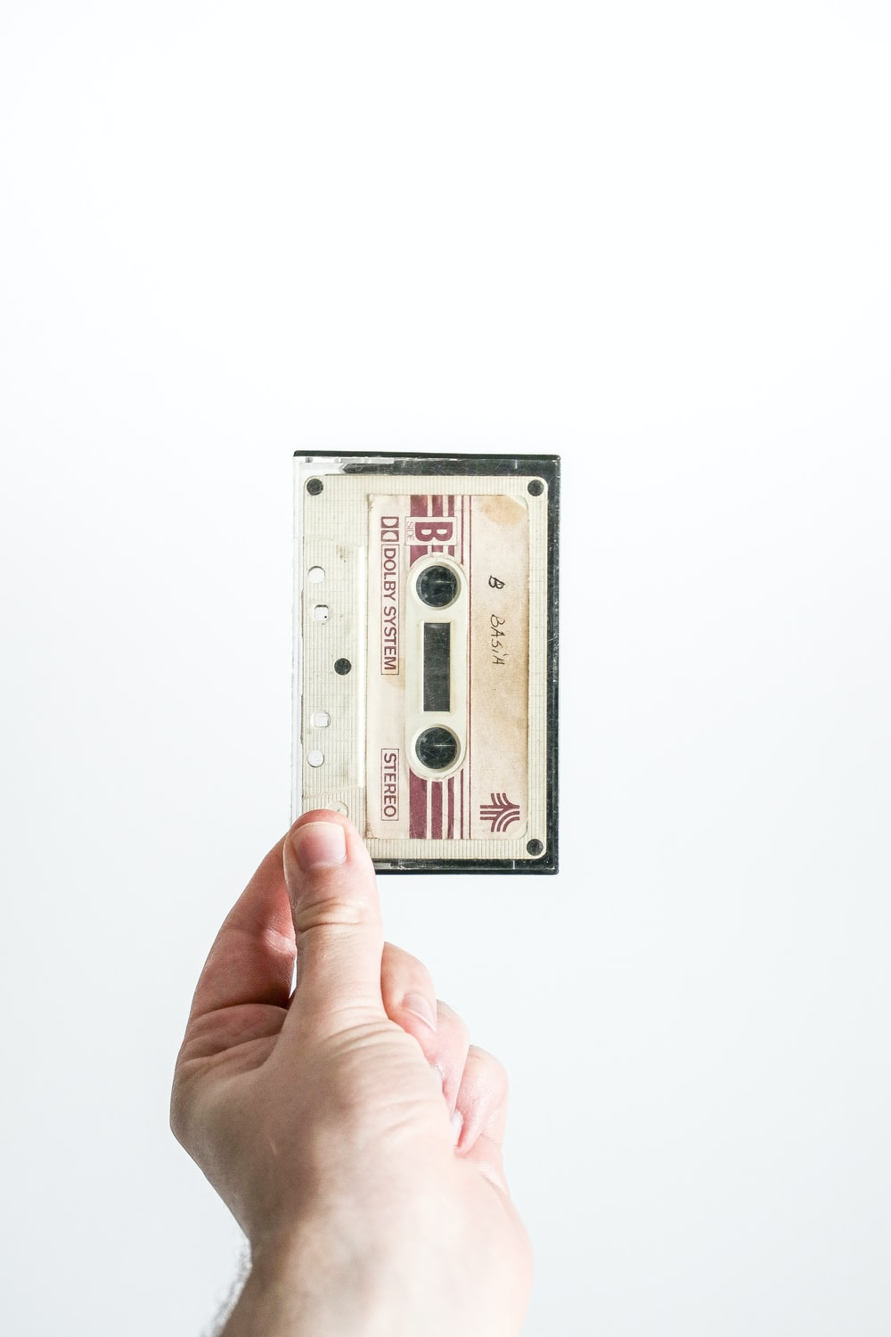 person holding brown cassette tape