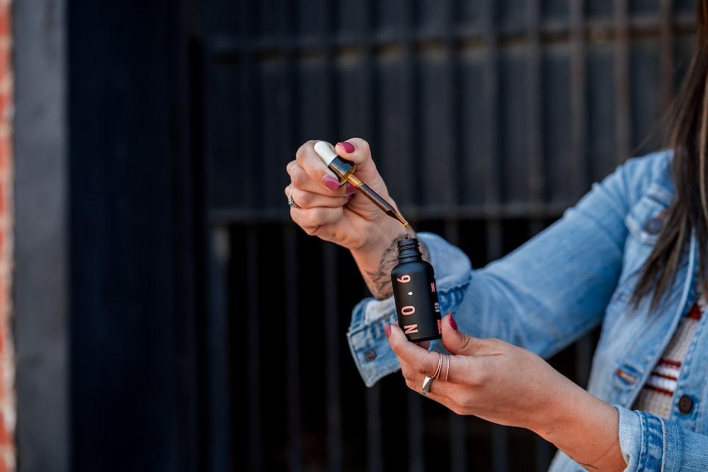 woman holding cosmetic drop bottle