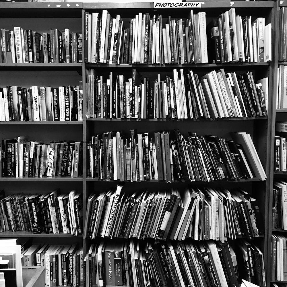 grayscale photo of books on a shelf