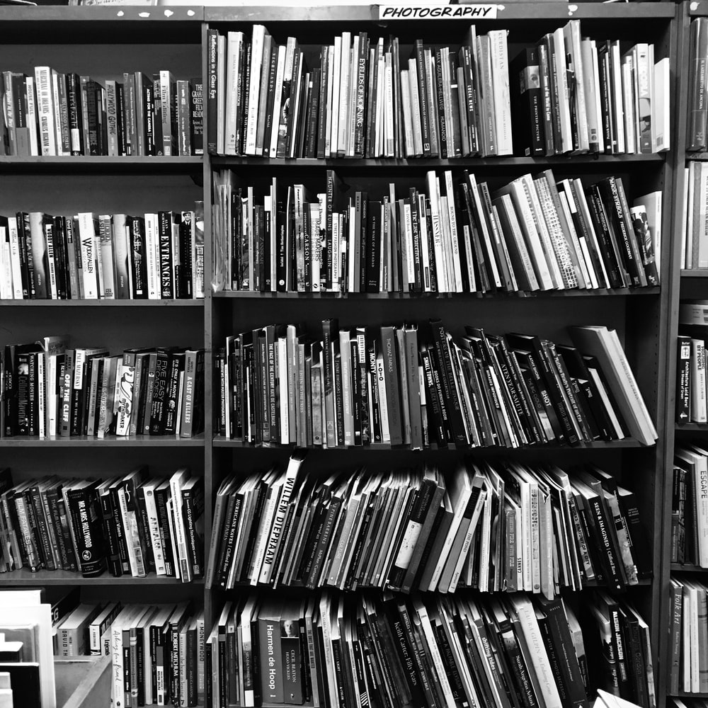grayscale photo of books on a shelf