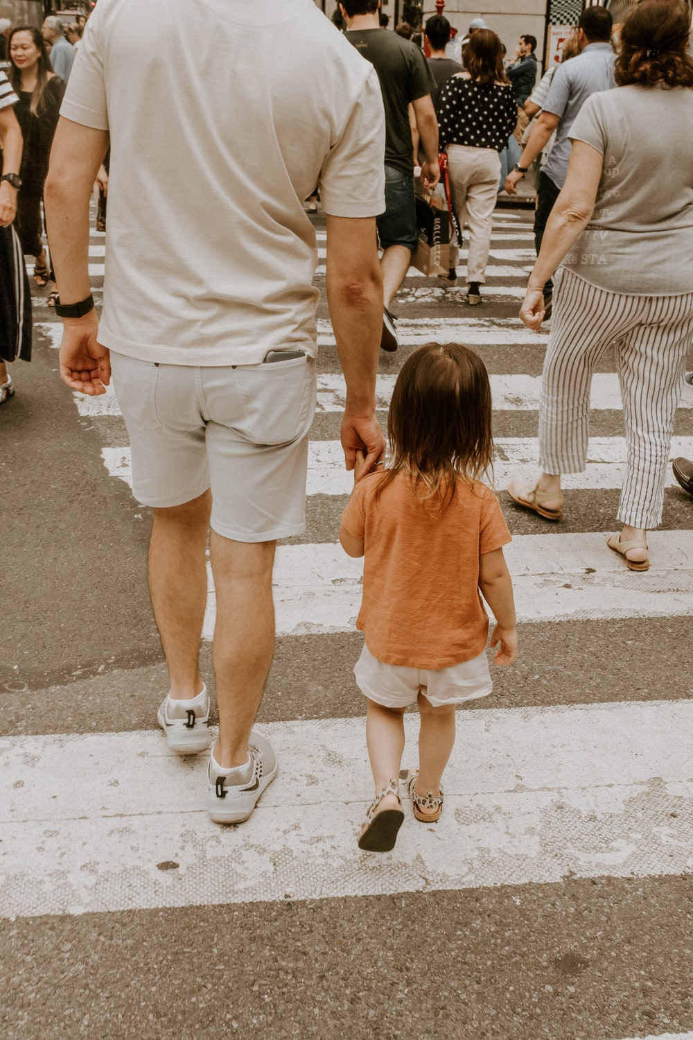 man walking on pedestrian lane with girl
