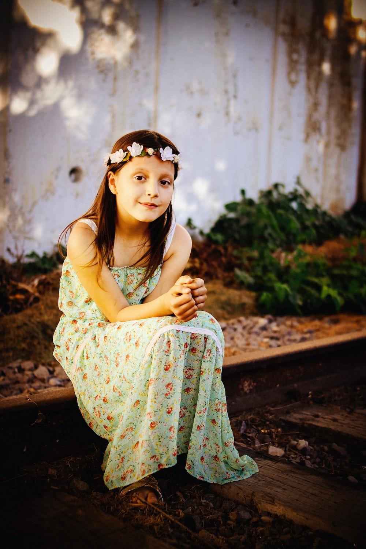 woman in floral maxi dress sitting on wood platform