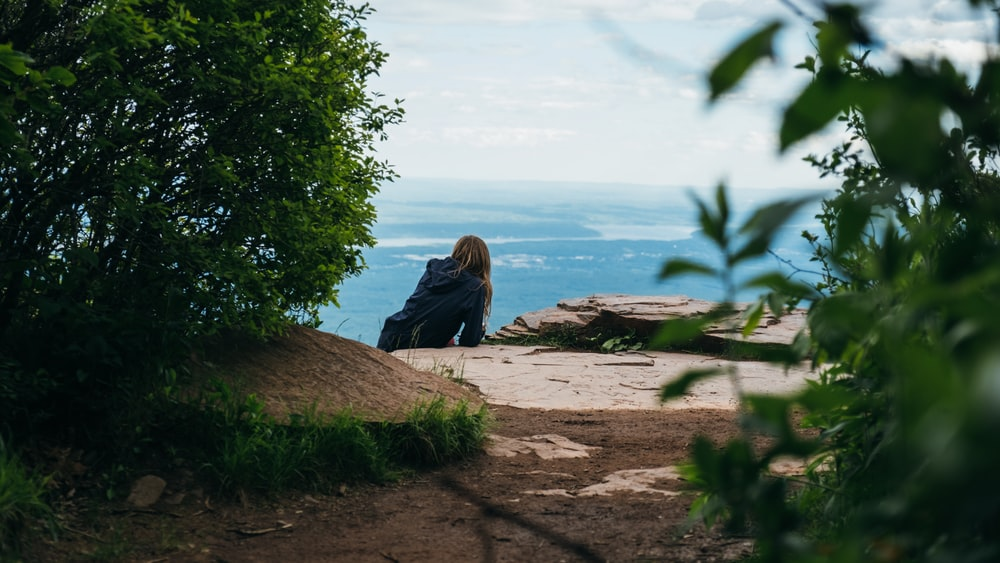 woman sitting on facing ocean