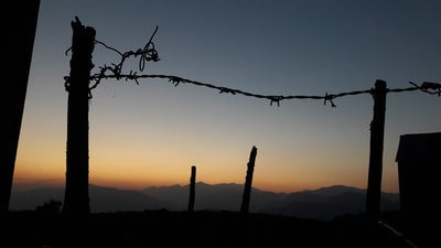 silhouette of fence and barbed wire