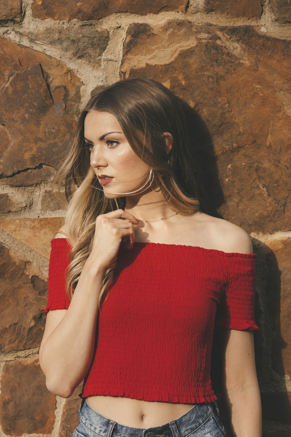 woman wearing red off-shoulder shirt leaning on wall
