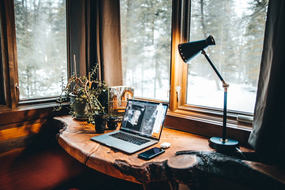 powered-on desk lamp near laptop computer