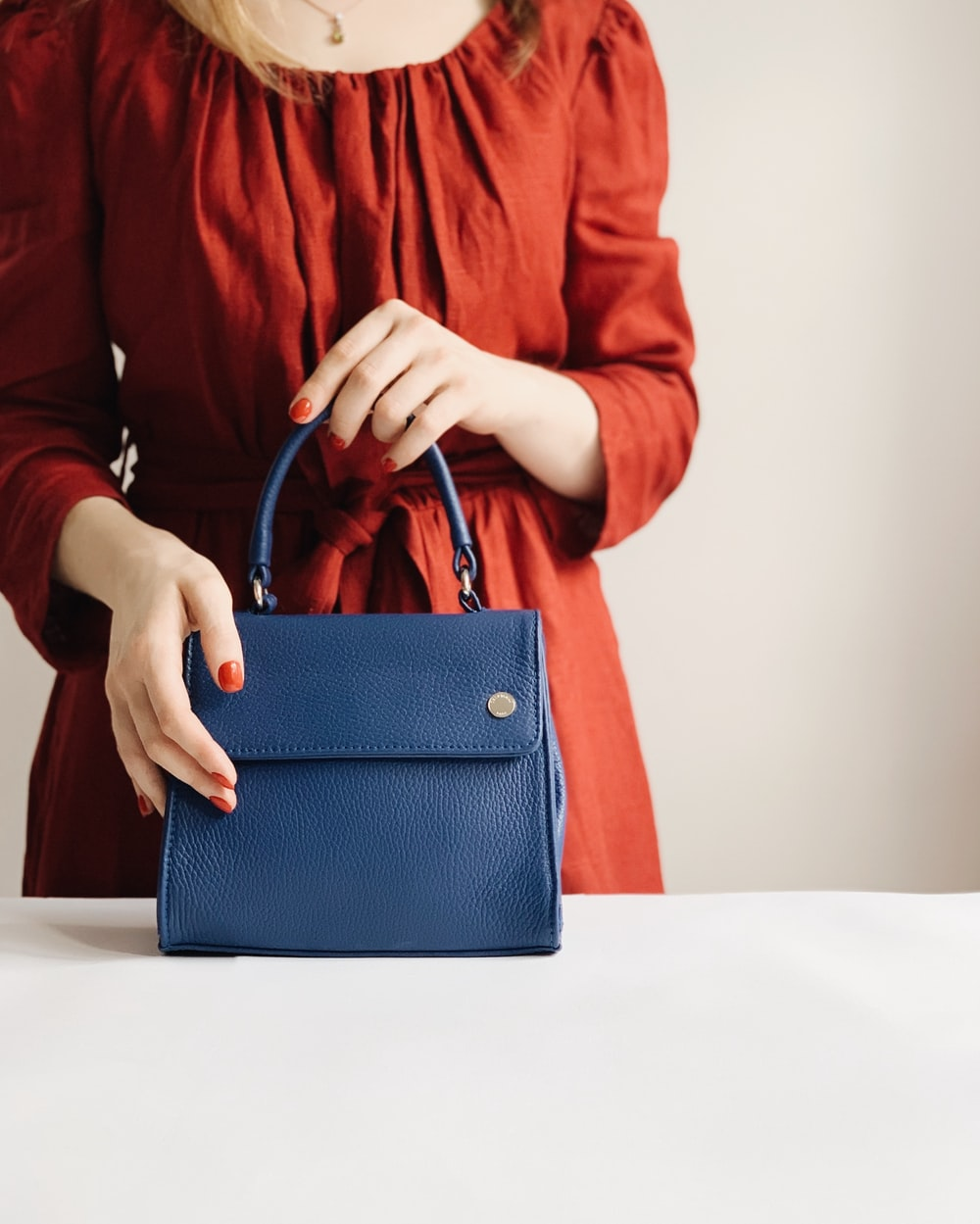 woman holding blue leather handbag
