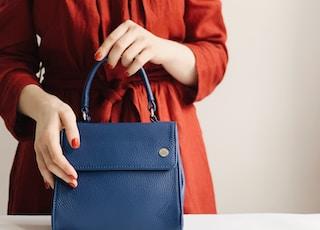 woman holding blue leather handbag