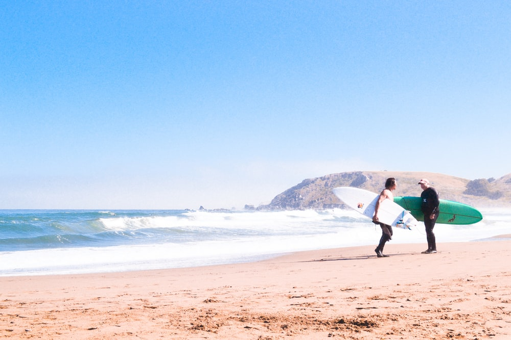 two man carrying surfboard beside seashore during daytime