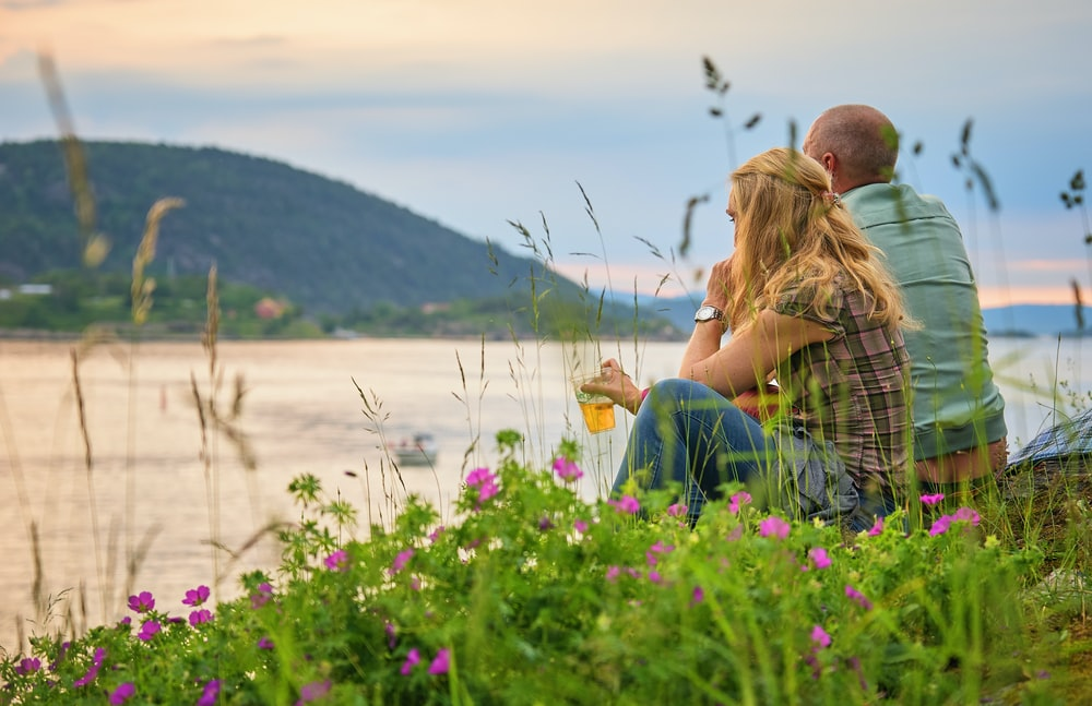 man and woman sitting on mountain facing on body of water during daytime