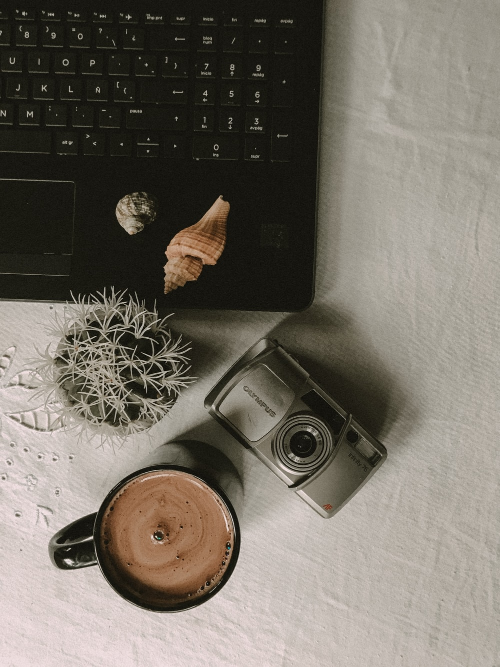 flat lay photography of cup of coffee beside gray camera