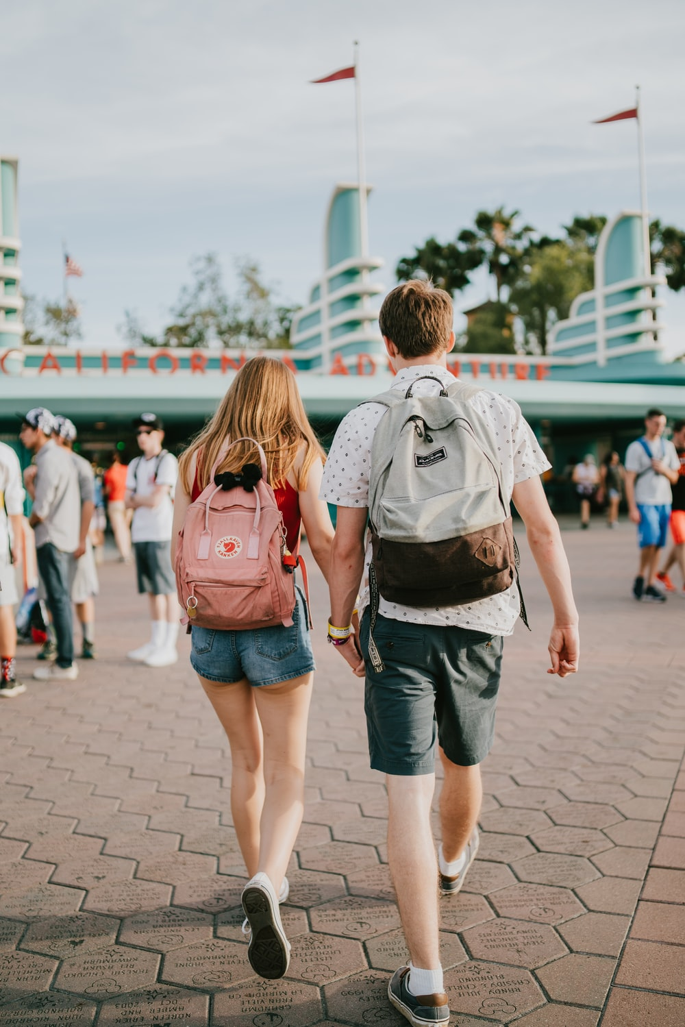 man and woman holding hands while walking towards building during daytime