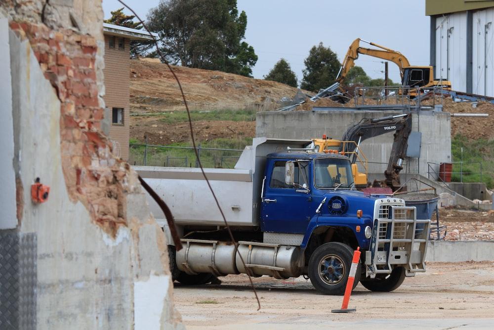 blue and white dump truck near house