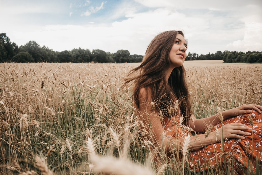 woman sitting on green grass field during daytime