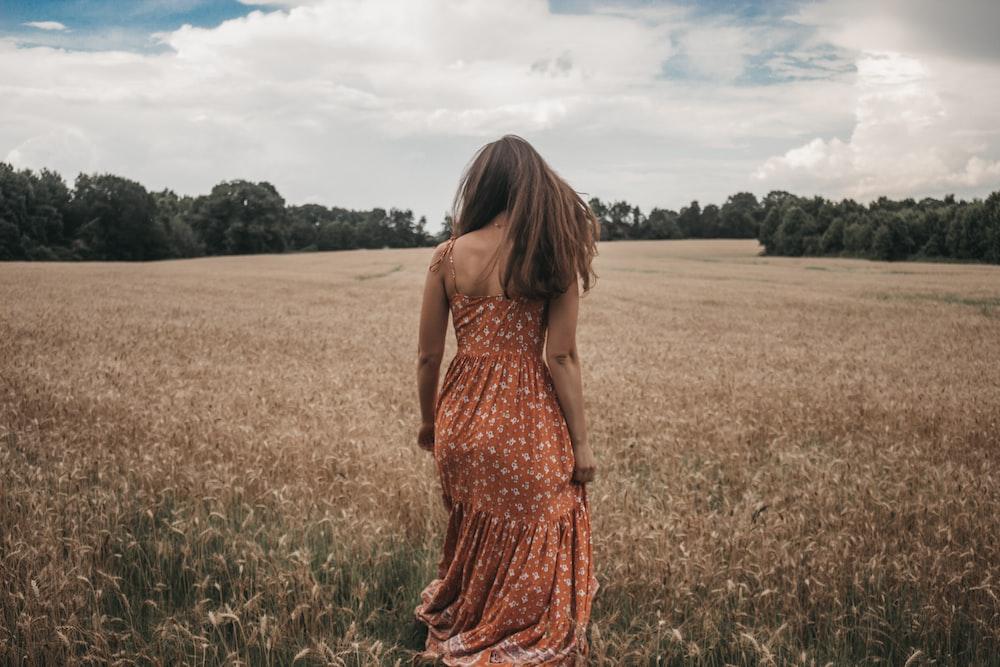 woman in orange dress on wheat field