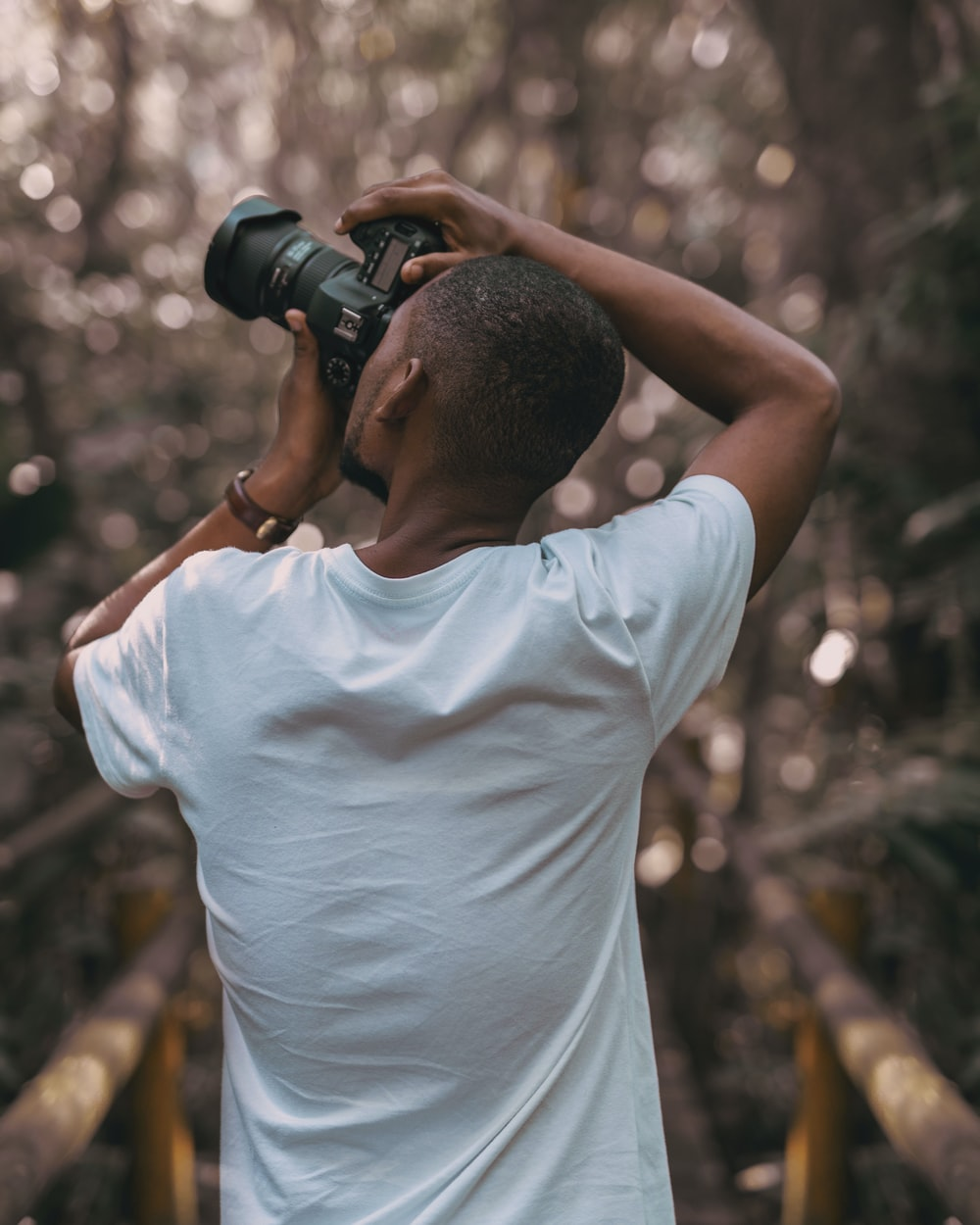 selective focus photography of a man in white t-shirt using a DSLR camera