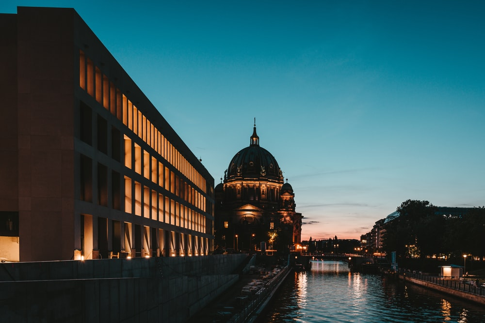 photography of river beside building during sunset