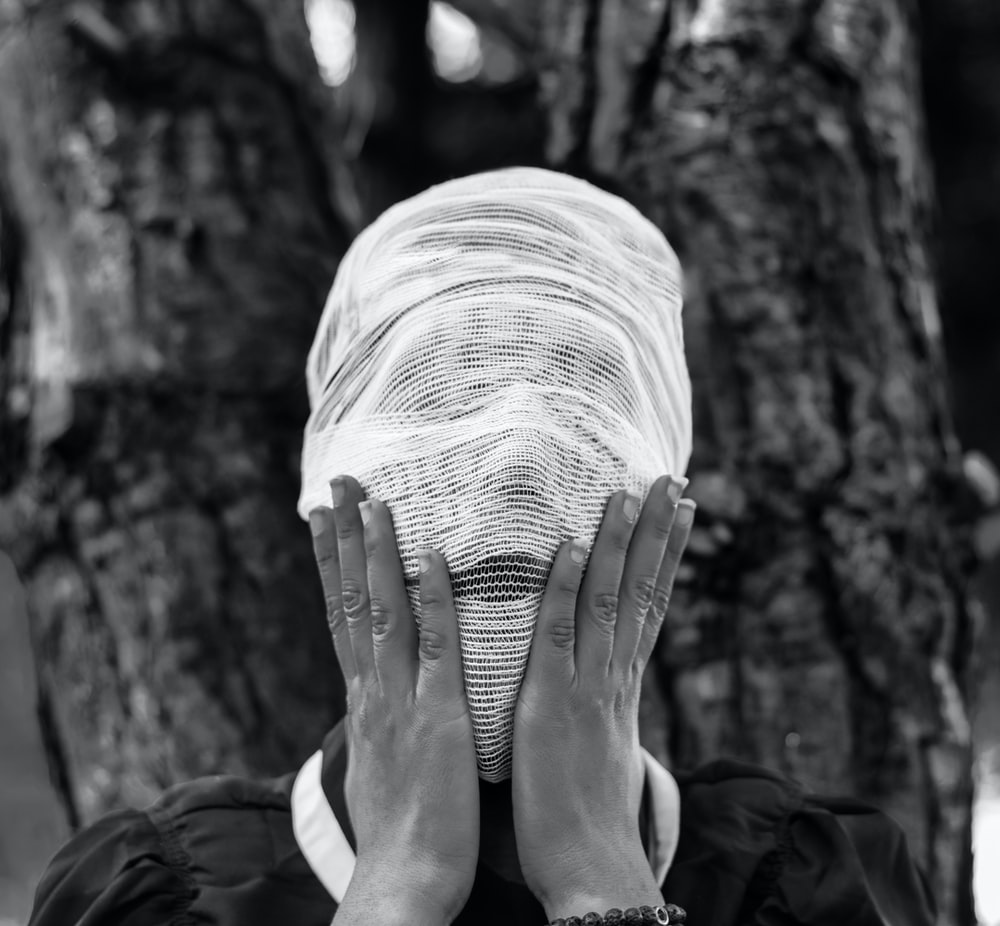 person wrapped face with white textile
