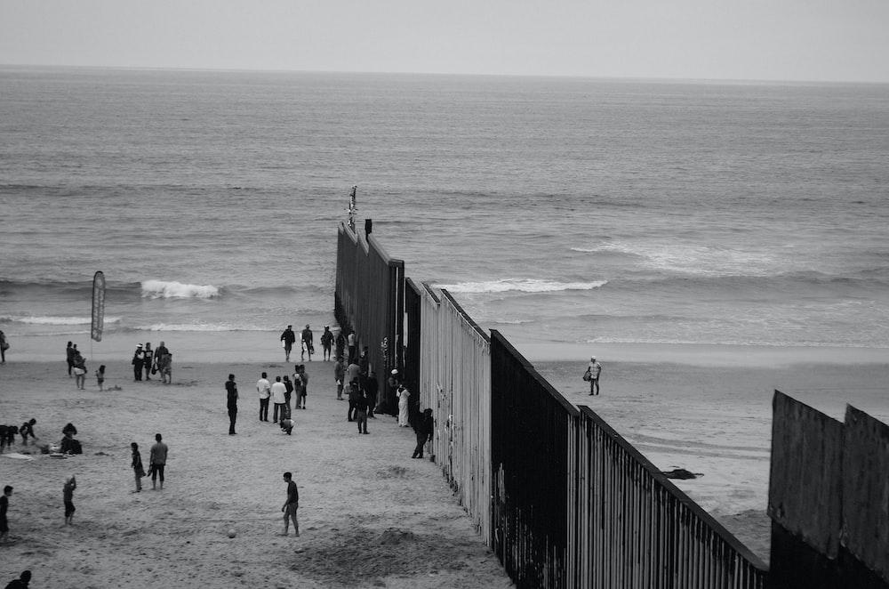 people in seashore near fence