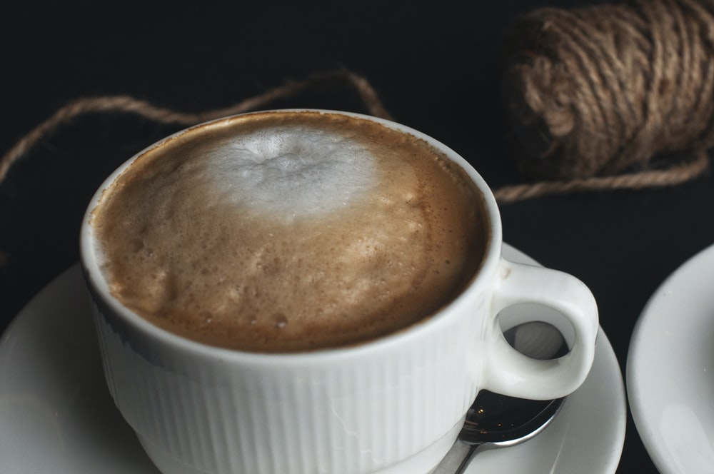 white cup filled by coffee