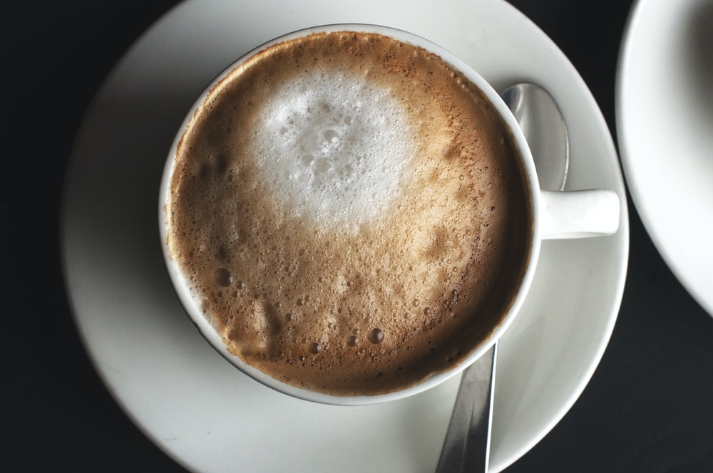 white ceramic coffee cup on saucer