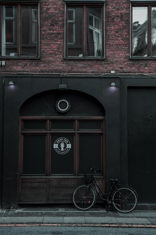 black city bike parked beside building during daytime