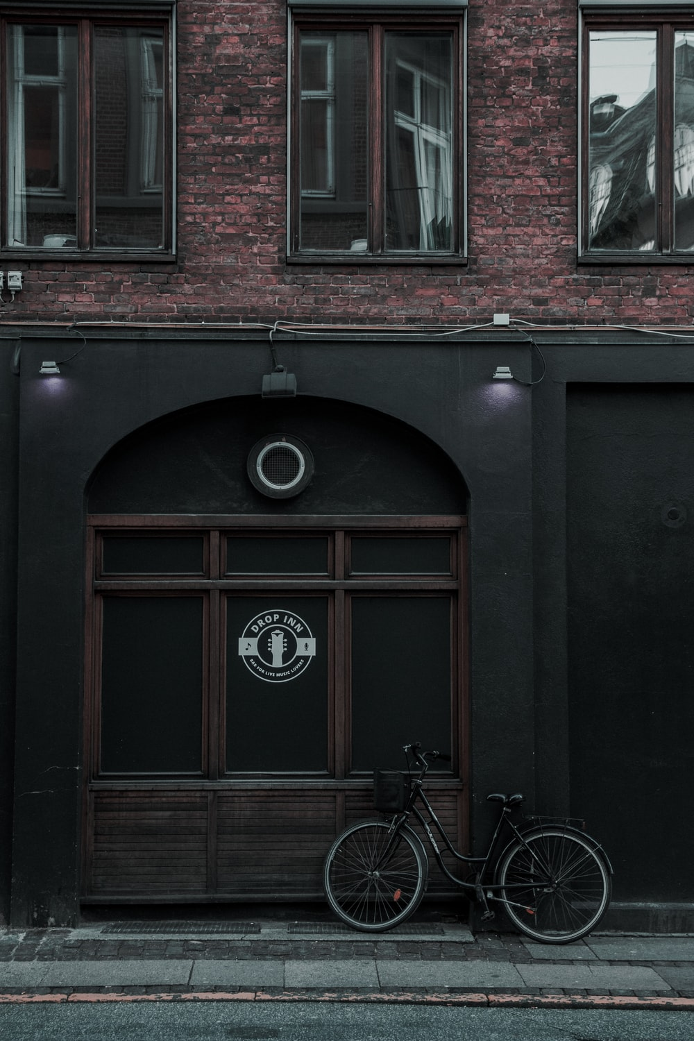 black city bike parked beside building during daytime