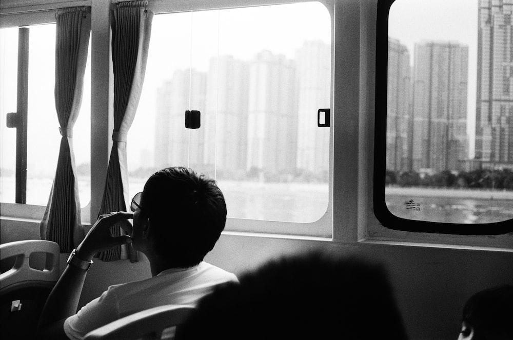 grayscale photo of man sitting beside window