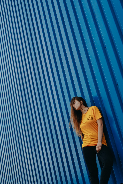 woman wearing yellow shirt leaning on blue wall