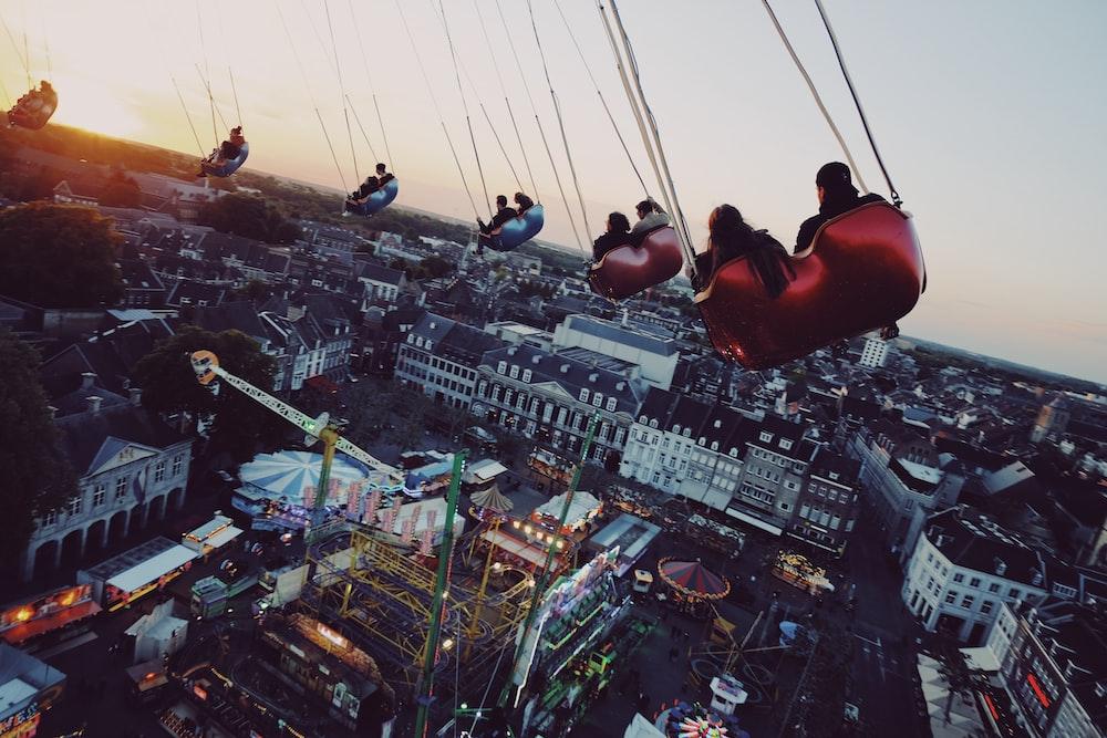 people riding on swing during daytime