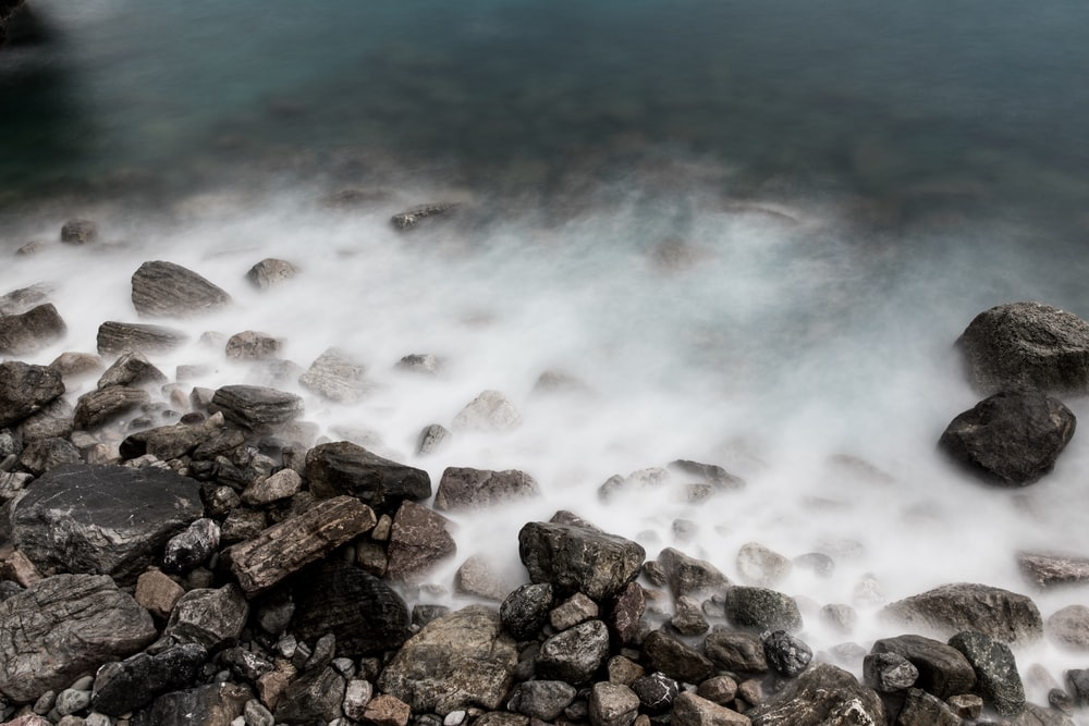 rock formation near body of water during daytime close-up photography