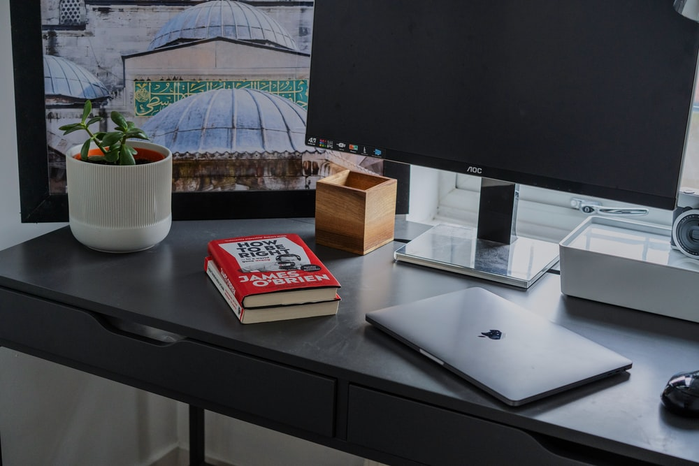 silver MacBook on black wooden table