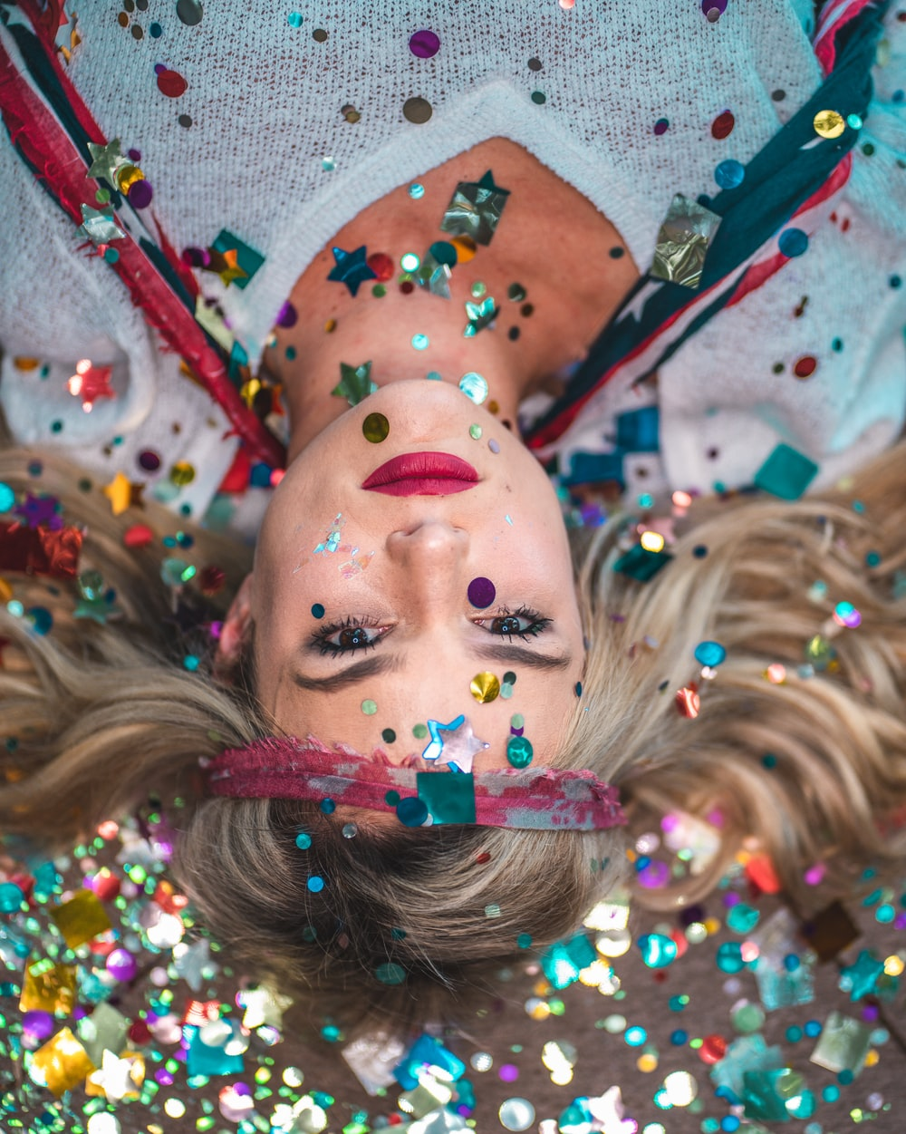 woman in white top covered with confettis while on floor