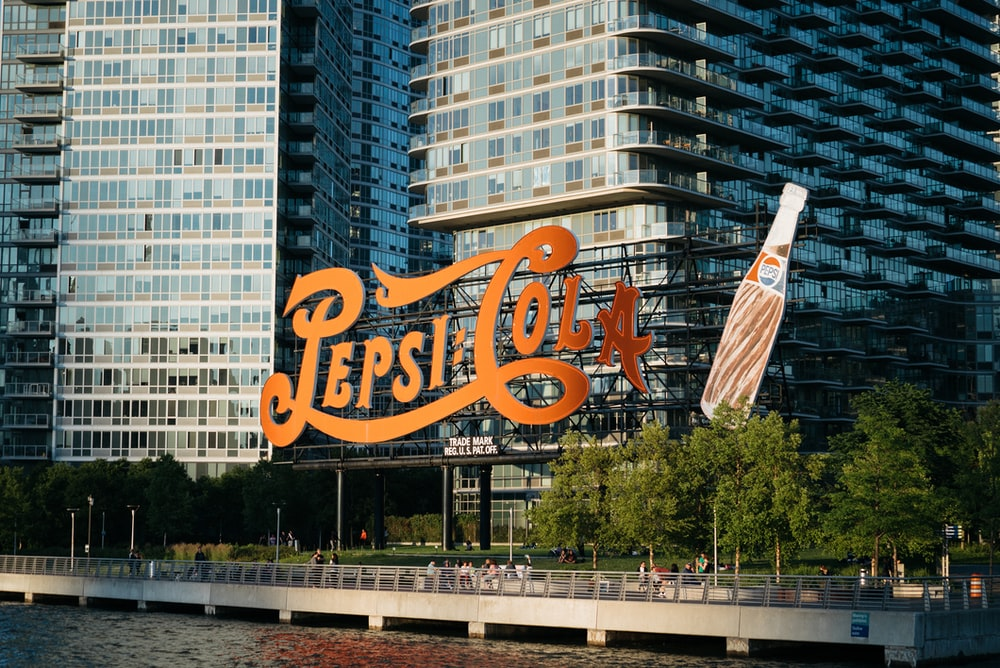 Pepsi-Cola signage near body of water