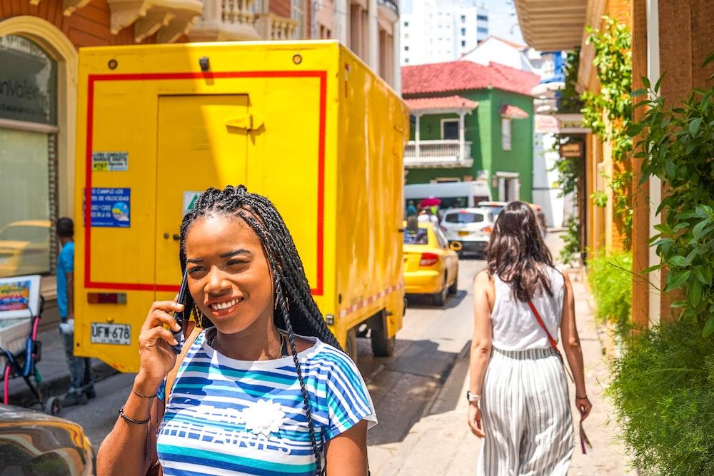 woman holding smartphone beside yellow box van