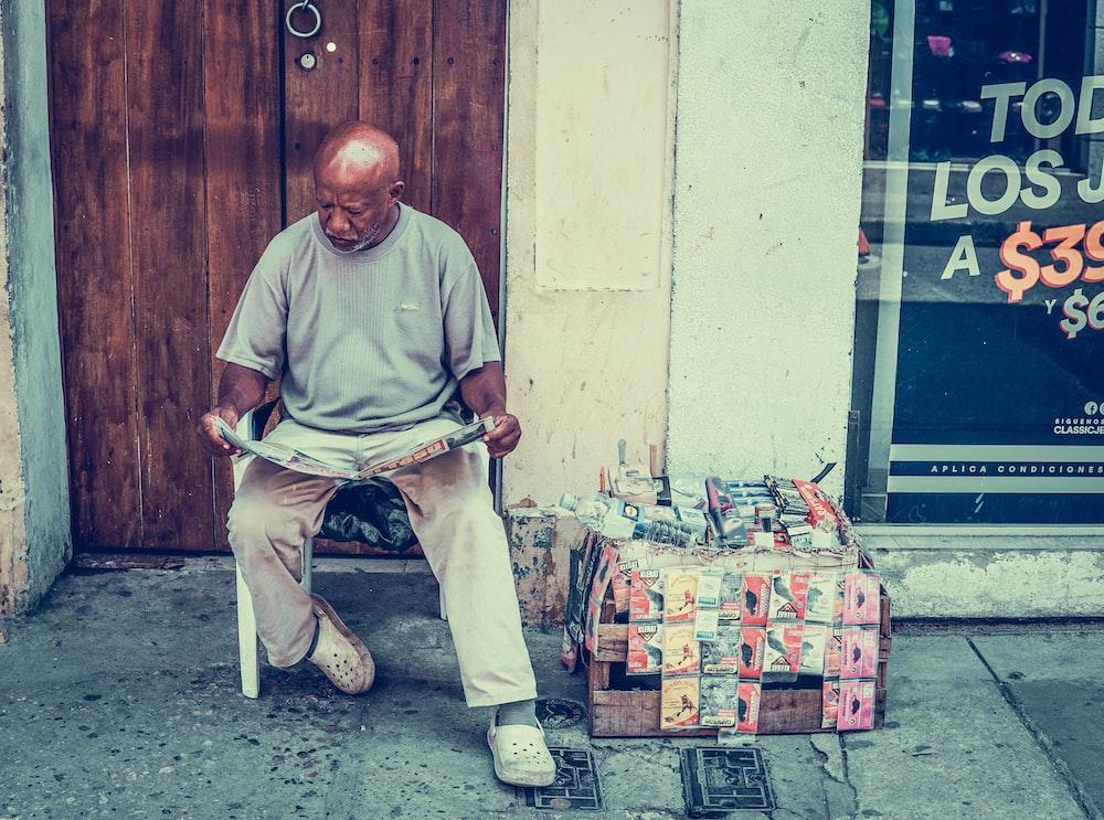 man reading newspaper near door