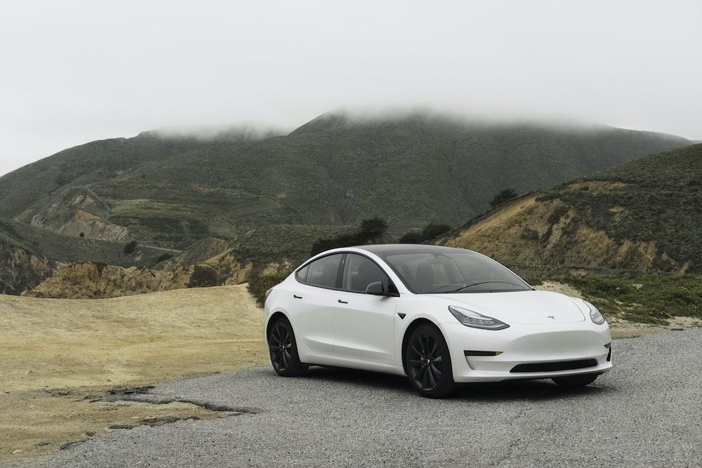white sedan parked beside mountain during daytime