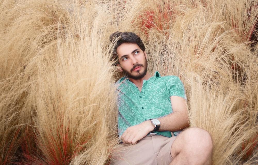 man lying on brown grass