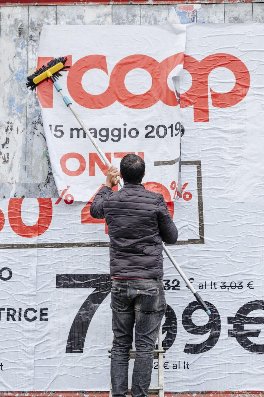 man in gray jacket brushing RCoop signage