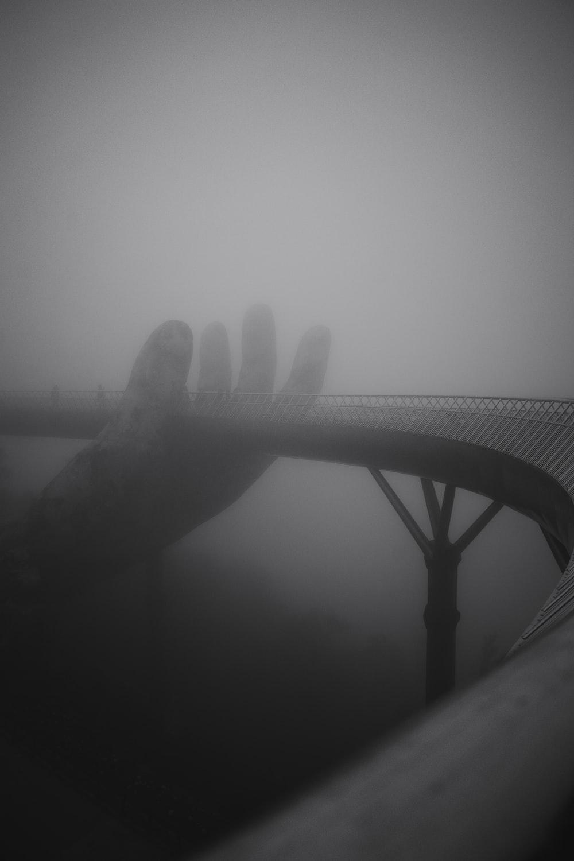 grayscale photography of hand holding bridge