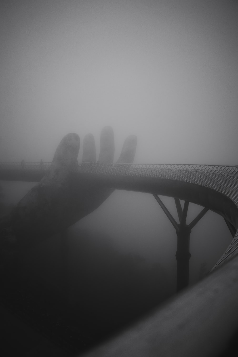 grayscale photography of hand holding bridge