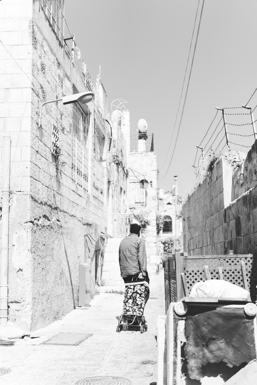 man on walkway in grayscale photo